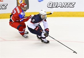 CHELYABINSK, RUSSIA - APRIL 26: USA's K'Andre Miller #19 skates with the puck while Russia's Yegor Zamula #12 chases him down during quarterfinal round action at the 2018 IIHF Ice Hockey U18 World Championship. (Photo by Andrea Cardin/HHOF-IIHF Images)